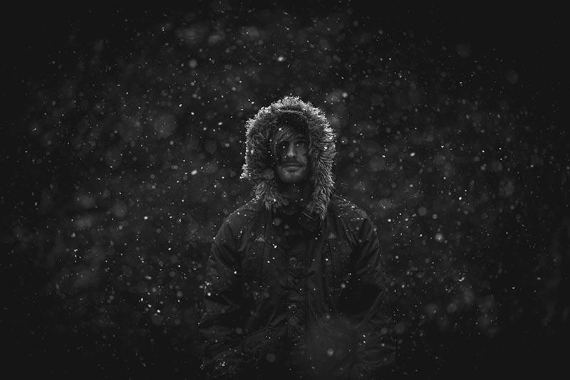 man in snow wearing a parka jacket