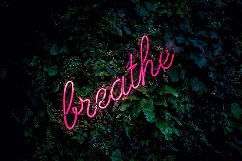 photo of neon sign saying breathe